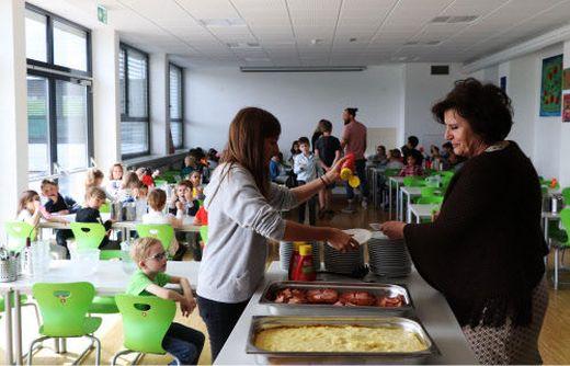 Direktorin und Lehrerin teilen im Speisesaal Essen aus